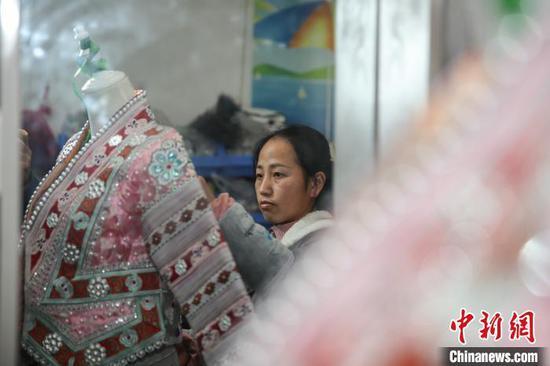 图为一名员工在整理半成品苗族服饰。 瞿宏伦 摄