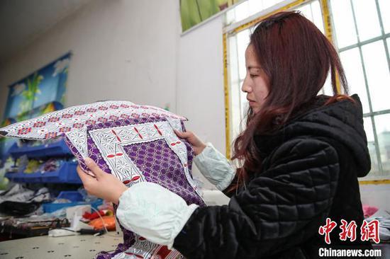 图为一名员工在查看苗族服饰上衣缝制情况。 瞿宏伦 摄