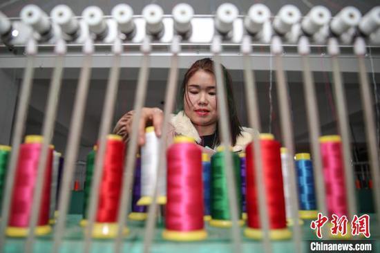 图为一名员工在整理刺绣机绣花线。 瞿宏伦 摄