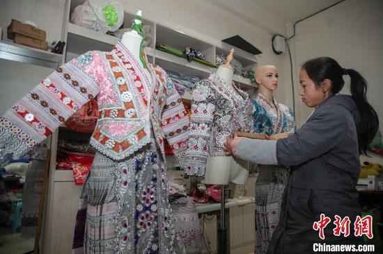 图为一名员工在确认半成品苗族服饰尺寸。 瞿宏伦 摄