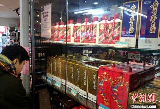 1月4日,市民在福建福州的一超市貴州茅臺酒專柜了解信息。 中新社記者 呂明 攝