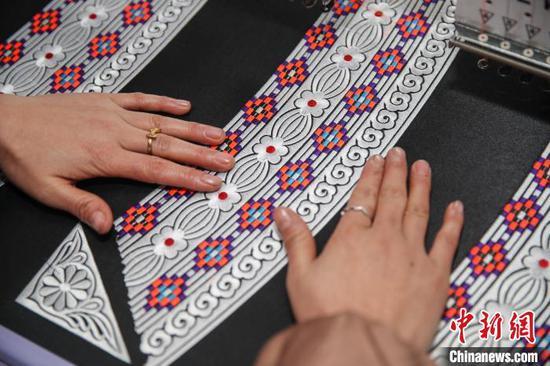图为一名员工在查看刺绣的质量。 瞿宏伦 摄