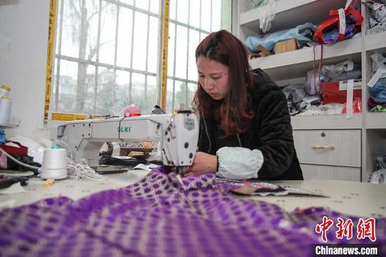 图为一名员工在缝制苗族服饰上衣。 瞿宏伦 摄