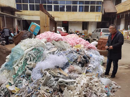 企業廠區內露天堆放著一堆廢布料、廢皮革。  金華市生態環境局浦江分局提供