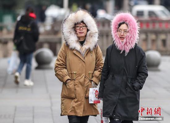 1月7日,受强冷空气影响,贵州省贵阳市气温骤降,最低气温在-4℃至-2℃之间。图为贵阳市民冒冷出行。 中新社记者 瞿宏伦 摄