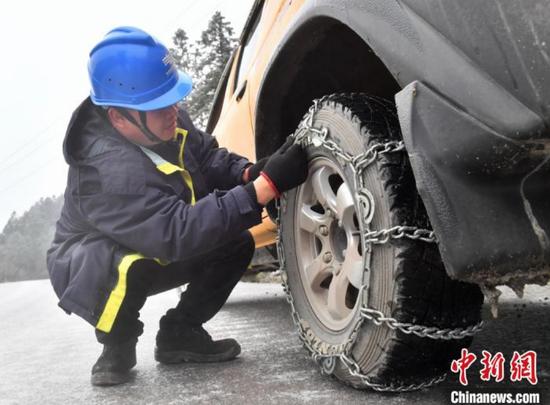 1月7日,贵阳供电局输电管理所驻点观冰员在开阳县双流镇用沙村巡线观冰途中安装汽车防滑链。 乔啟明 摄