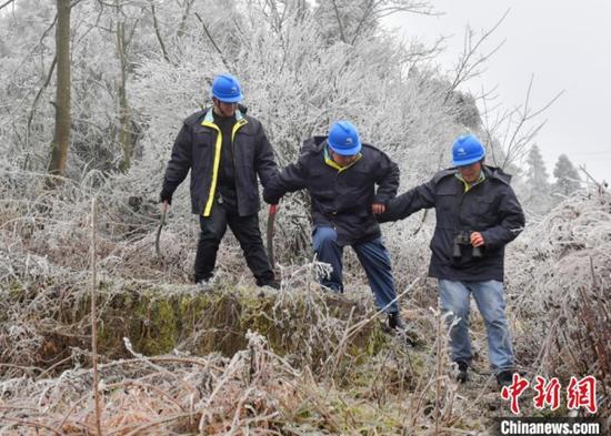 1月7日,贵阳供电局输电管理所驻点观冰员相互搀扶着在贵阳市开阳县双流镇用沙村巡线观冰。 乔啟明 摄