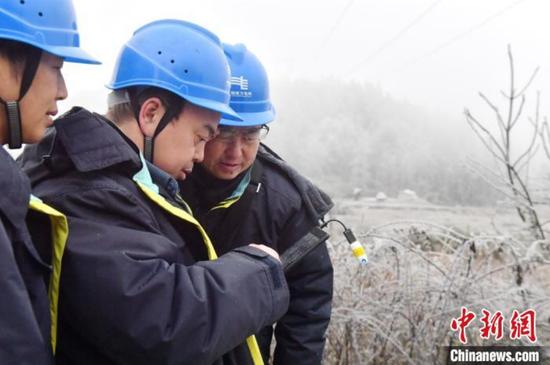 1月7日,贵阳供电局输电管理所驻点观冰员在开阳县双流镇用沙村巡线时分析覆冰数据。 乔啟明 摄
