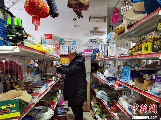 图为安景绪在整理货柜上的商品。 周燕玲 摄