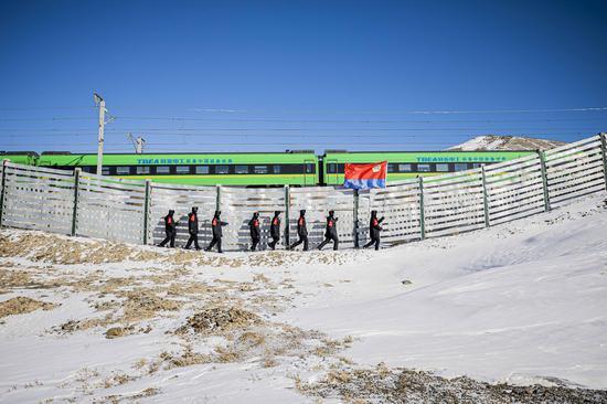 """在首个""""中国人民警察节""""当日一列""""复兴号""""动车与巡线民警并列而行。"""