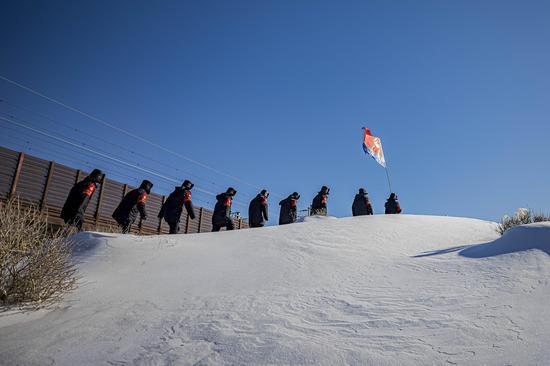 """民警在首个""""中国人民警察节""""当日踏着风吹雪巡查兰新高铁线路。"""