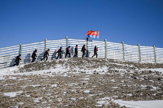 """民警在首个""""中国人民警察节""""当日沿着挡雪墙巡查兰新高铁线路。"""