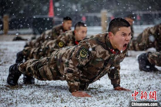 圖為武警貴州總隊機動支隊官兵雪地中開展體能訓練?!钦苊?攝