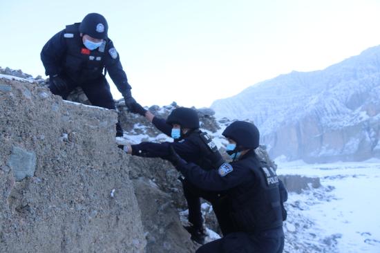 图为民警相互协助攀越障碍。