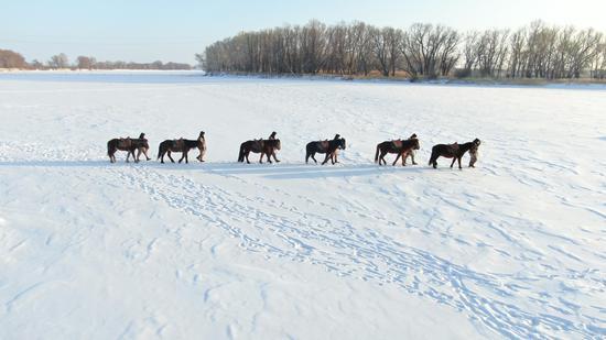 官兵乘马行走在边境线。