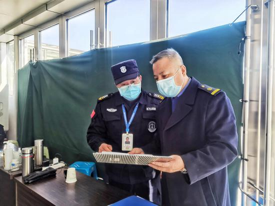 缙云西站工作人员检查进站口旅客测温情况。 庄卫东 摄