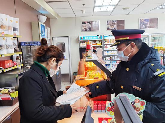 缙云西站工作人员指导检查候车厅商铺测温记录。  庄卫东 摄