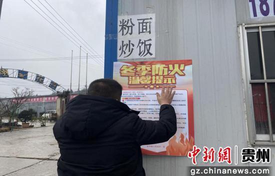 工作人员张贴消防安全海报
