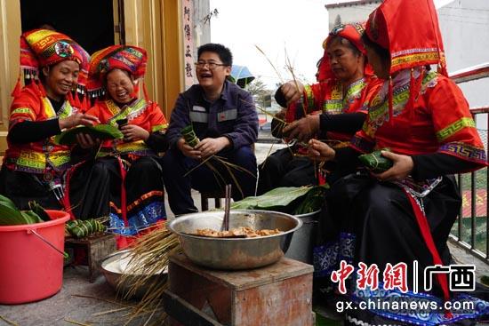 南方电网广西南宁供电局派驻上林云桃村第一书记黄建敏和村民一起包粽子。敬敏  摄