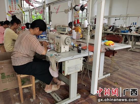 2020年6月,横县南乡镇高义村扶贫车间里,工人们在缝纫机前飞快的组装玩具  韦艳 摄