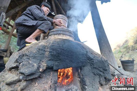 图为一名侗族榨油师傅在蒸茶籽粉。 吴德军 摄