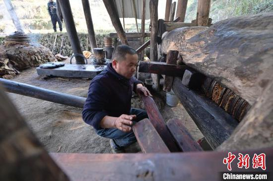 图为一名侗族榨油师傅在装楔子。 吴德军 摄