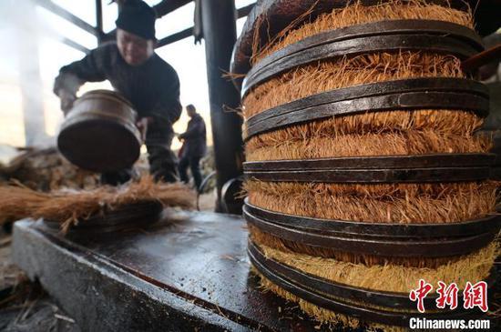 图为一名侗族榨油师傅在制作茶饼。 吴德军 摄