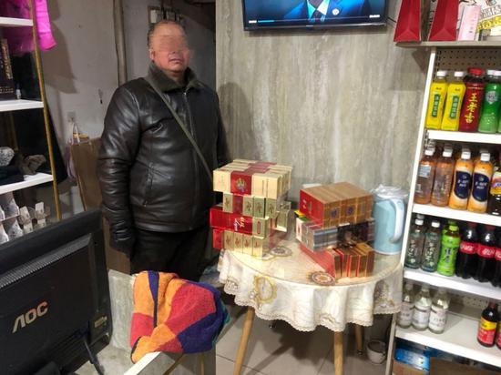 冯某某及其被当场查获非法经营的卷烟。  桐庐县烟草专卖局 供图