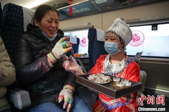 图为穿着少数民族服装的列车员郑燕将贵州特色年货分发给旅客品尝。 瞿宏伦 摄