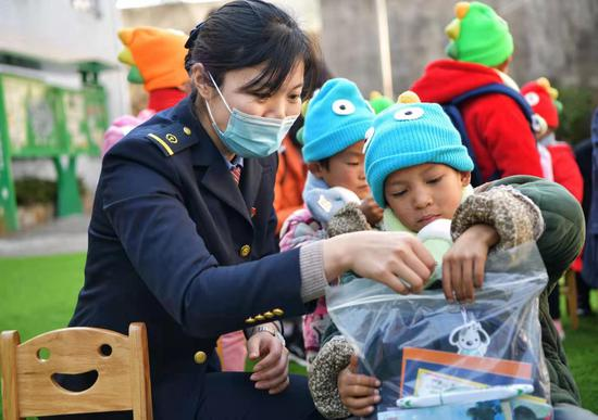 缙云西站工作人员向木栗村留守儿童捐赠学习物品。  庄卫东 摄