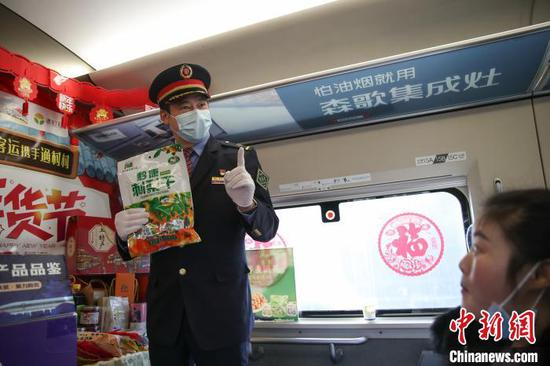 图为列车长令狐绍红在介绍贵州特色年货。瞿宏伦 摄