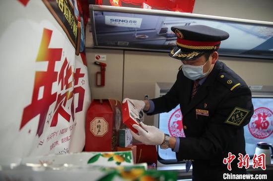 图为列车长令狐绍红在整理贵州特色年货。 瞿宏伦 摄
