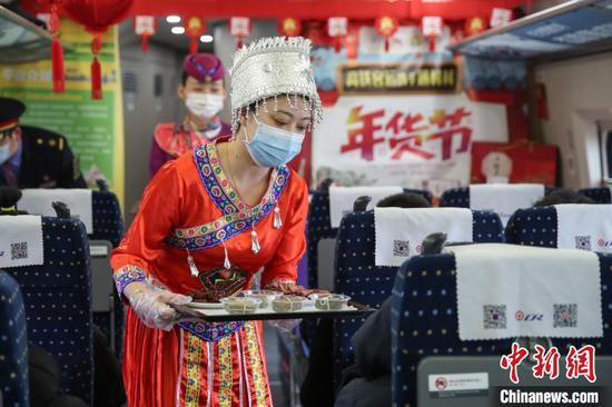 图为穿着少数民族服装的列车员郑燕在推介贵州特色年货。瞿宏伦 摄
