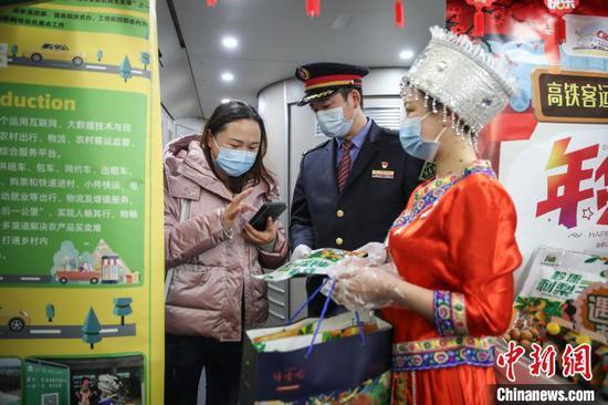 图为一位旅客在购买贵州特色年货。 瞿宏伦 摄