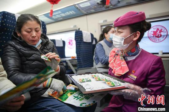 图为列车员王茜将贵州特色年货分发给旅客品尝。 瞿宏伦 摄