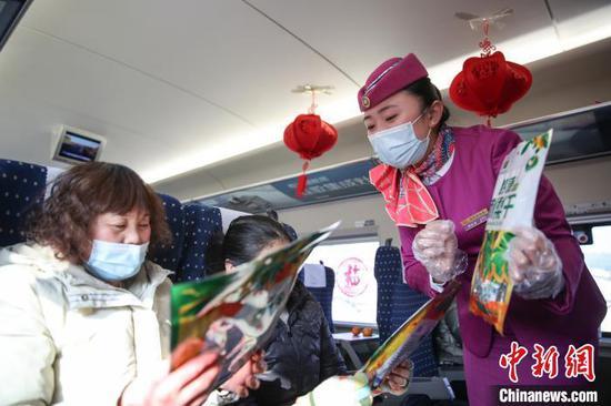 图为列车员杨婷婷在介绍贵州特色年货。 瞿宏伦 摄
