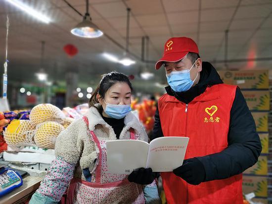 志愿者给辖区农贸市场营业人员宣传党的十九届五中全会精神。