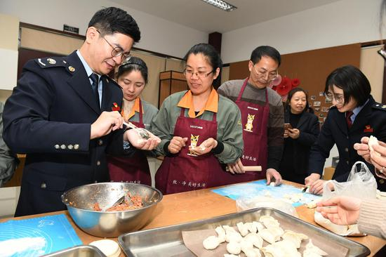 税务人员和企业职工一起包饺子。黄静波 摄