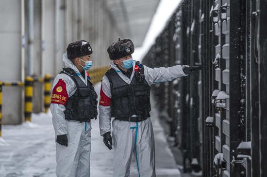 民警在雪中对待运货车车门闭锁情况进行安全检查。