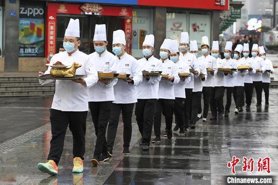 戴勇攀与传菜员们将烹饪完成的湘菜送入展馆。 杨华峰 摄