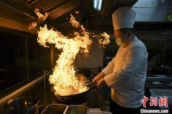 戴勇攀进行湘菜烹饪。 杨华峰 摄