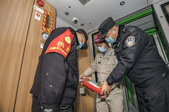 民警会同客检中心安全员对动车消防器材进行安全检查。