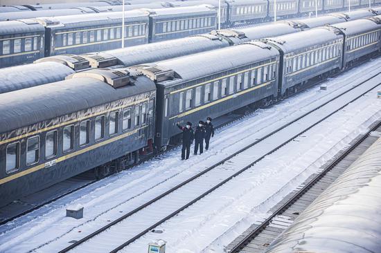 民警对普速旅客列车停留场车体进行安全巡查。