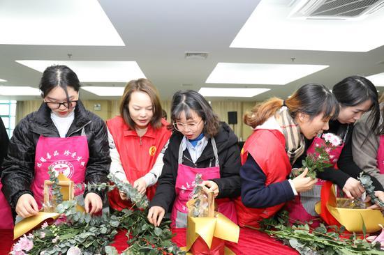志愿者指导外来务工人员插花 何伟卫供图
