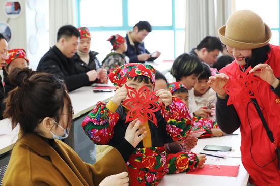 外来务工人员子女互相展示刚完成的剪纸 何伟卫供图