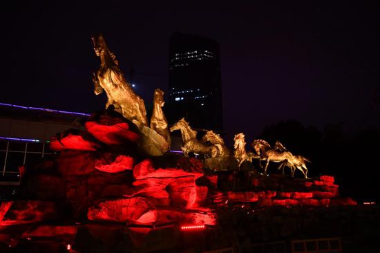 灯光映衬下的八匹马雕塑