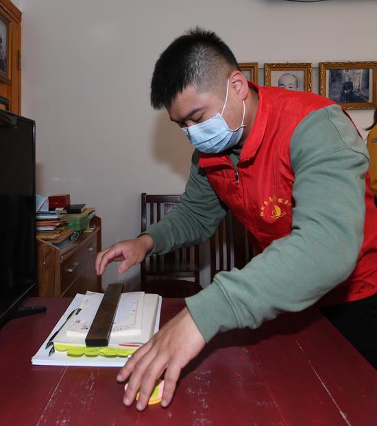 仁庄镇志愿者为留守老人整理房间。  王刚 摄