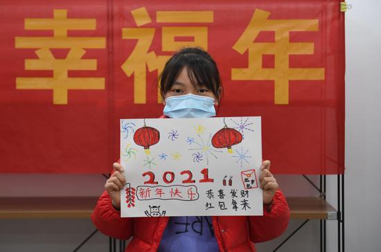 一位小朋友展示其新年主题绘画作品。  王刚 摄