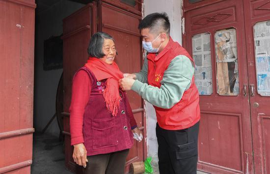 仁庄镇志愿者为留守老人佩戴围巾。  王刚 摄