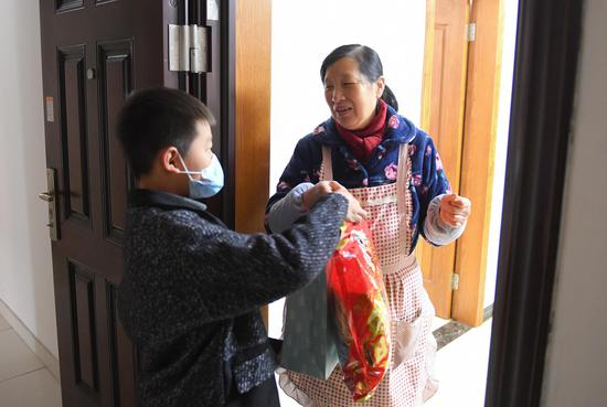 留杭儿童为空巢老人赠送新年礼包。  王刚 摄